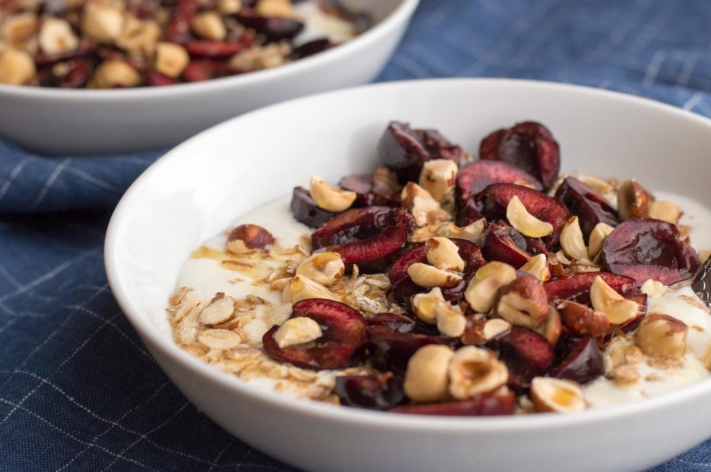 fresh cherry breakfast bowl with yogurt and hazelnuts